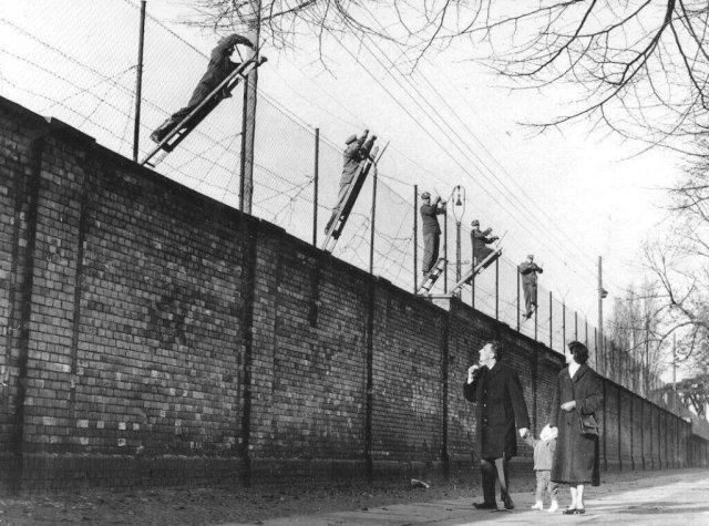 Пограничники Восточного Берлина увеличивают высоту берлинской стены с помощью колючей проволоки. Германия, 19 ноября 1961 года.