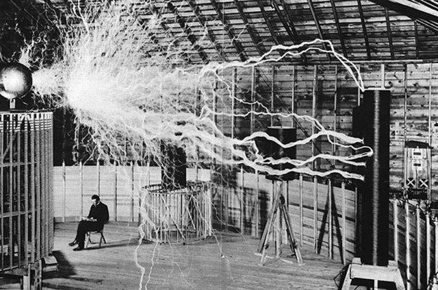 """Никола Тесла и его """"усиливающий передатчик"""" в лаборатории."""