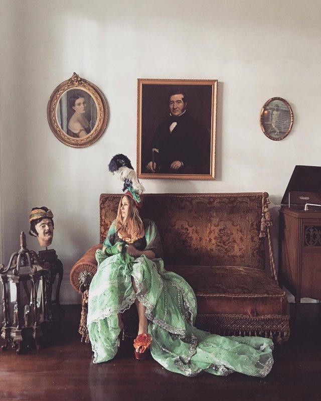 Дженнифер Кулидж - легендарная мама Стифлера на старом диване во время фотосессии