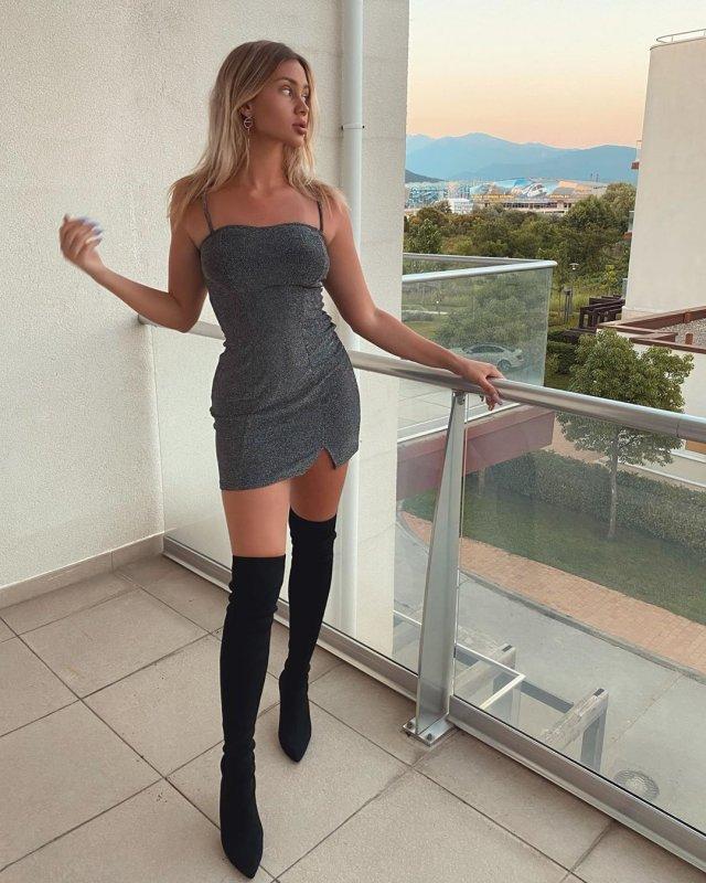 Mash Milash в черных сапогах и сером платье в номере отеля