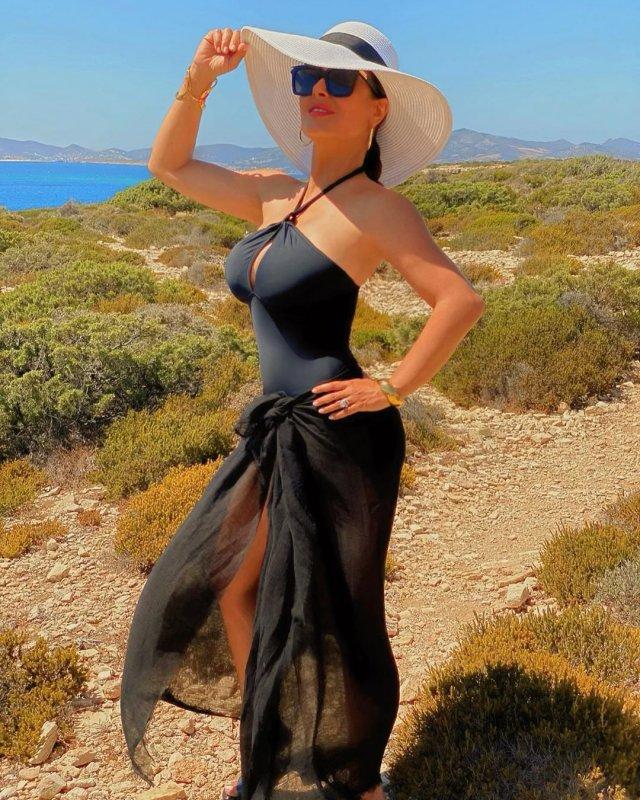 Сальма Хайек в черном платье и белой шляпе на острове