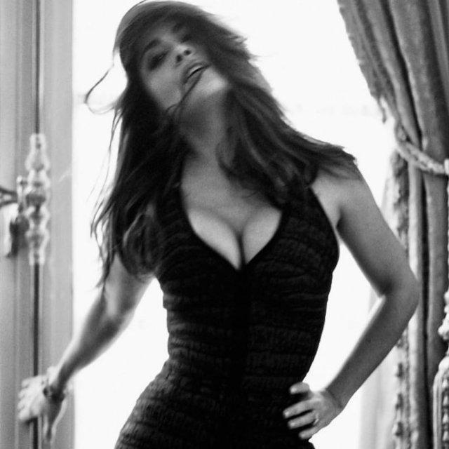 Сальма Хайек в черном платье на фоне окна