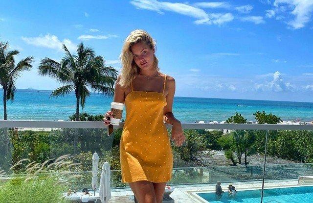 Софья Жук на балконе стоит в желтом платье