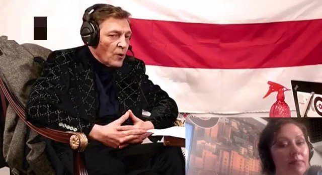 Александр Невзоров в черном костюме на фоне флага Беларуси