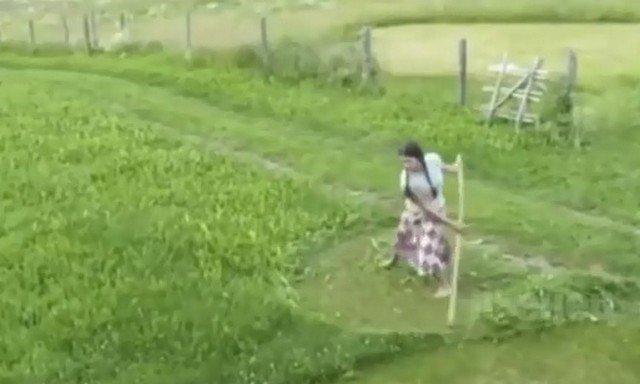 Девушка косит траву
