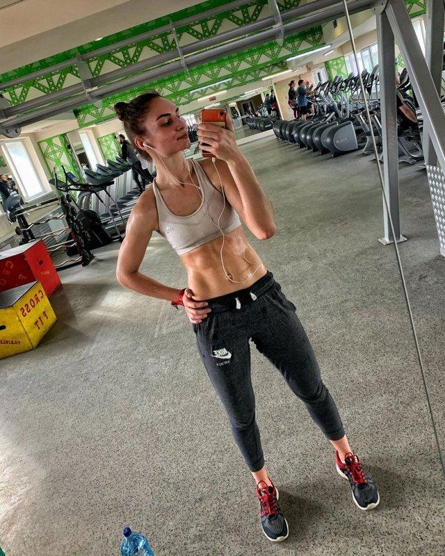 Анастасия Бадина в белом топе и черных штанах в спортзале