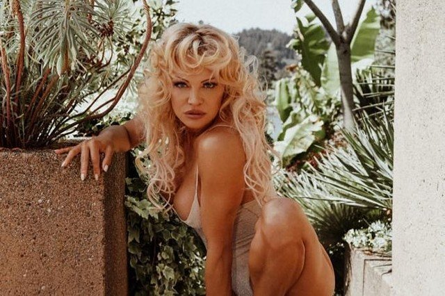 Памела Андерсон в белом купальнике на фоне зелени