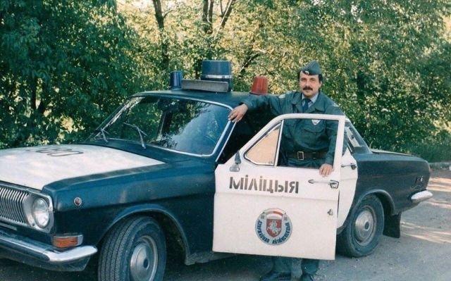 Белорусский милиционер рядом со своей патрульной Волгой