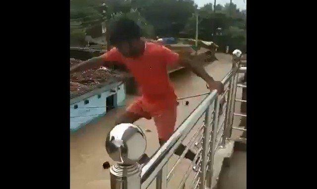 Мужчина в красном прыгает в воду с балкона