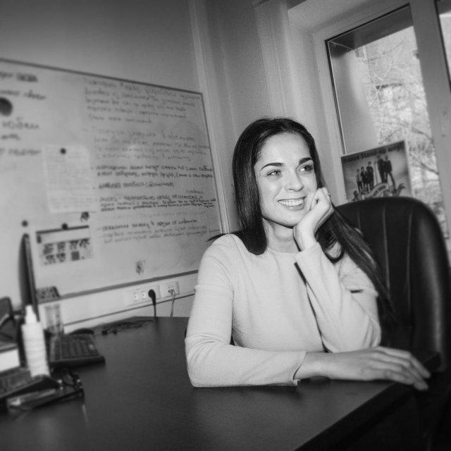 Юлия Ахмедова в кофте за столом