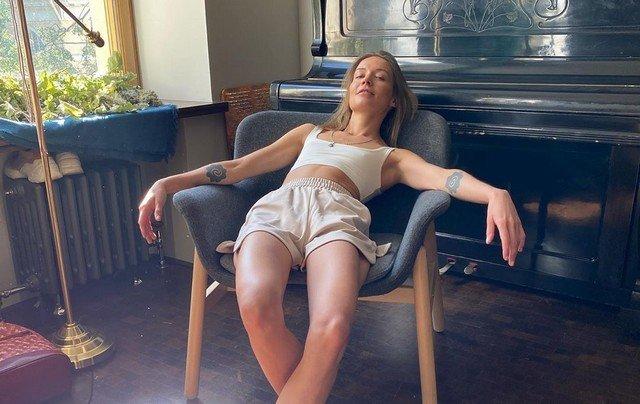 Марина Кацуба лежит на кресле в белом топе и шортах на фоне пианино