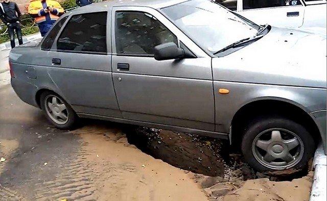 Автомобиль ВАЗ висит над дырой в асфальте
