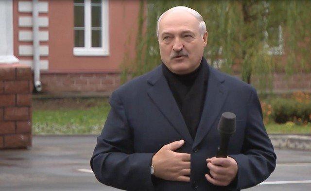 Александр Лукашенко в темном пальто и черном шарфе стоит с микрофоном и рассказывает о мороженом.