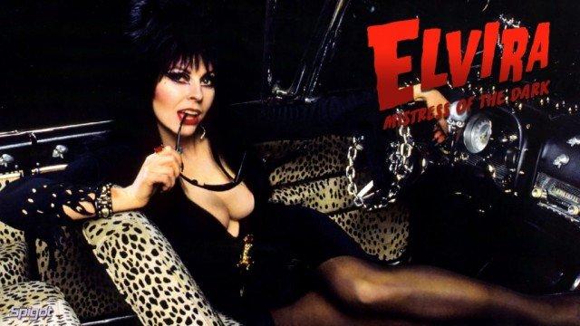Кассандра Петерсон (Эльвира - повелительница тьмы)  в черном платье на леоапрдовом диване
