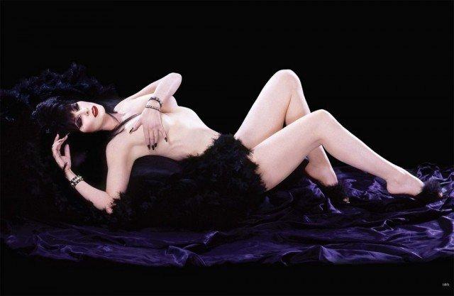 Кассандра Петерсон (Эльвира - повелительница тьмы)  обнаженная лежит на пуфе