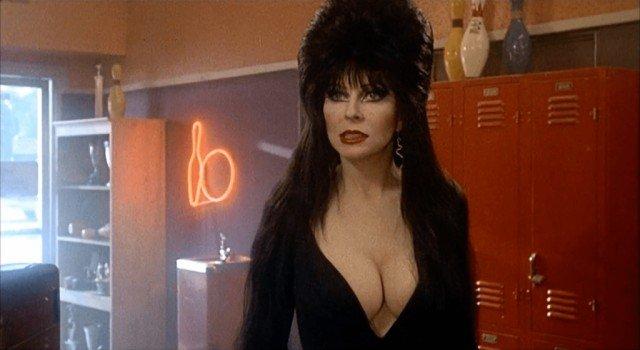 Кассандра Петерсон (Эльвира - повелительница тьмы) в черном платье на фоне красных шкафов