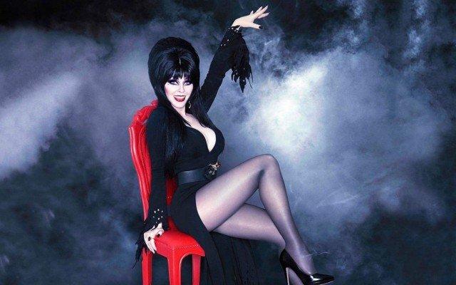 Кассандра Петерсон (Эльвира - повелительница тьмы) в черном платье на красном стуле
