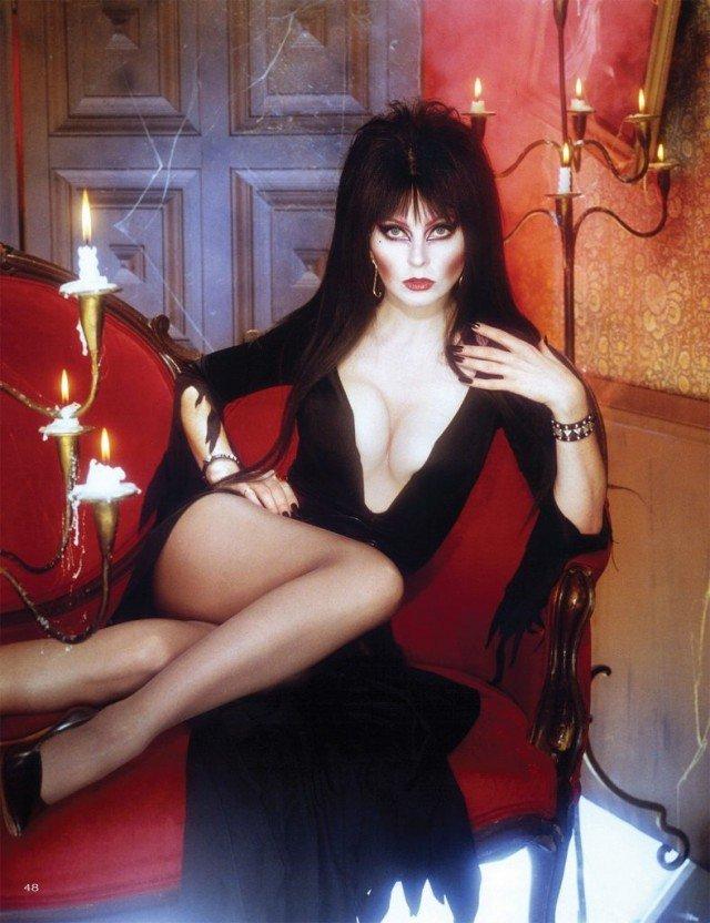 Кассандра Петерсон (Эльвира - повелительница тьмы) в черном платье на красном диване