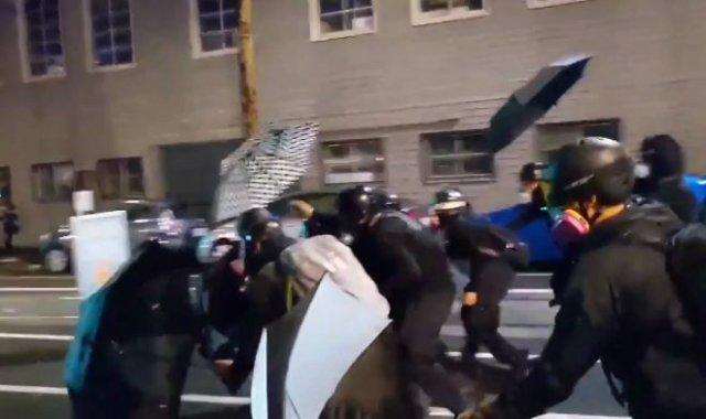 Протестующие из Портленда прикрываются зонтами от спецназа