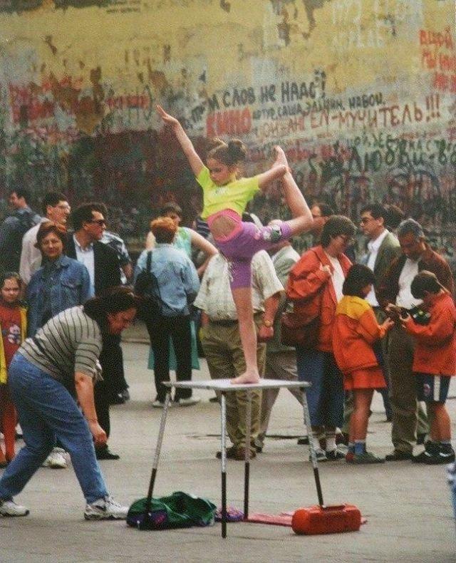 Девочка выполняет акробатические упражнения под музыку для заработка денег, 90-е.