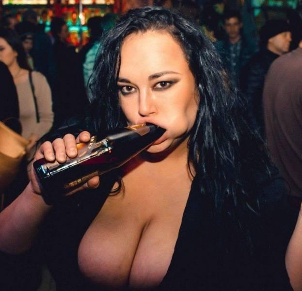 Девушка засовывает бутылку из под пива в рот