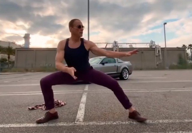 Жан-Клод Ван Дамм танцует в черной майке и фиолетовых штанах в клипе Aaron.