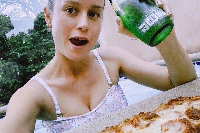Бри Ларсон в белом платье ест пиццу