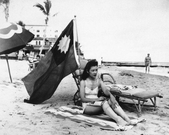 Китаянка Руфь Ли загорает под китайским флагом, чтобы её не перепутали с японкой, декабрь 1941 года, США