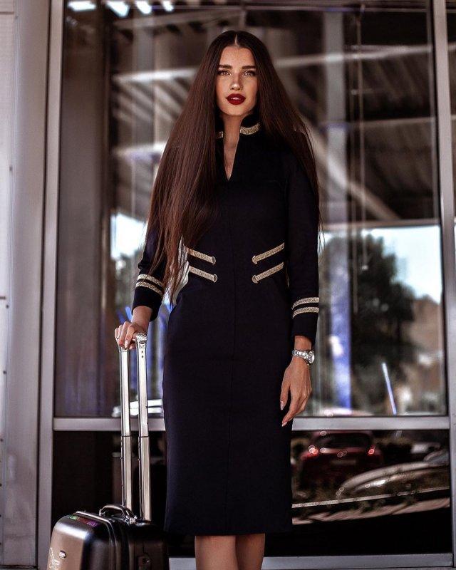 Стюардесса Алена Глухова в форме с чемоданом выходит из аэропорта