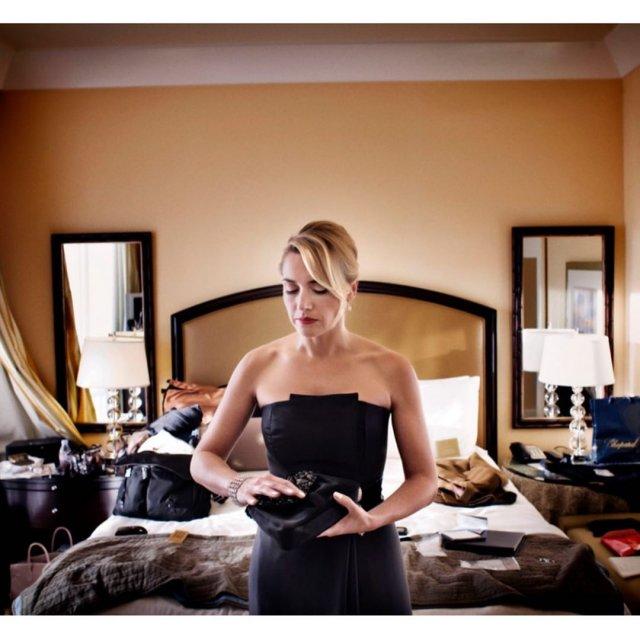 Кейт Уинслет в черном платье собирается в номере отеля