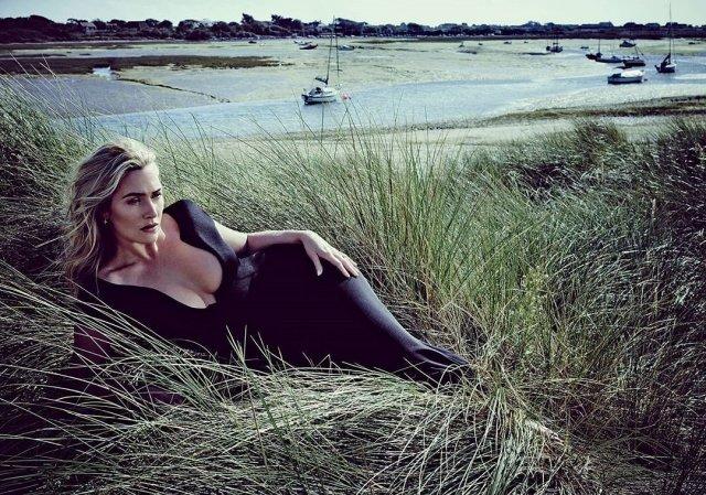 Кейт Уинслет в черном платье с глубоким декольте лежит на траве