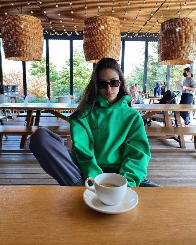 Виктория Короткова в зеленой кофте пьет кофе