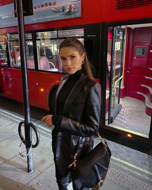 Виктория Короткова в черной одежде на фоне красного автобуса