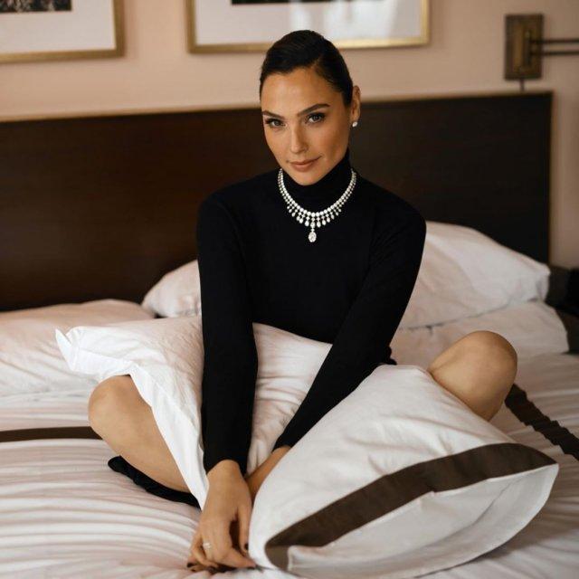 Анджелина Джоли в черной кофте с подушкой в руках