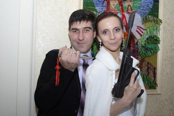 пара позирует с оружием