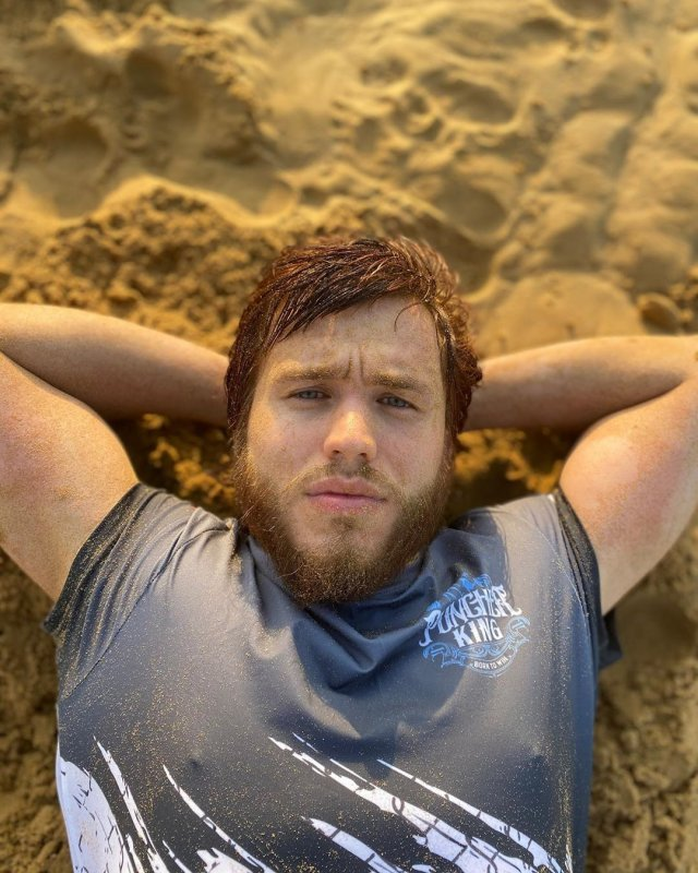 Сергей Романович с бородой в футболке на песке