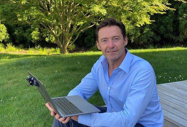 Хью Джекман в синей рубашке с ноутбуком
