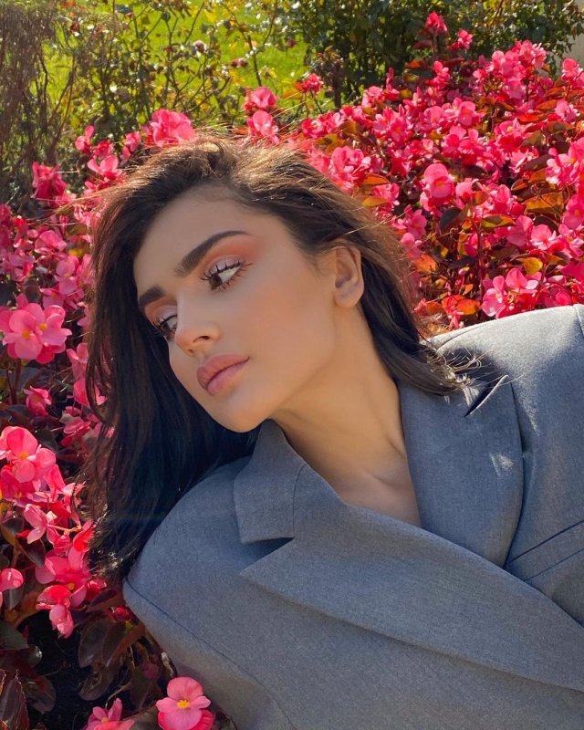 Дина Саева в сером пиджаке на фоне цветов