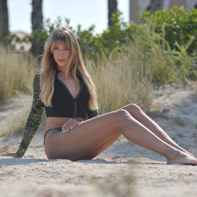 Леся Никитюк на пляже в черной кофте