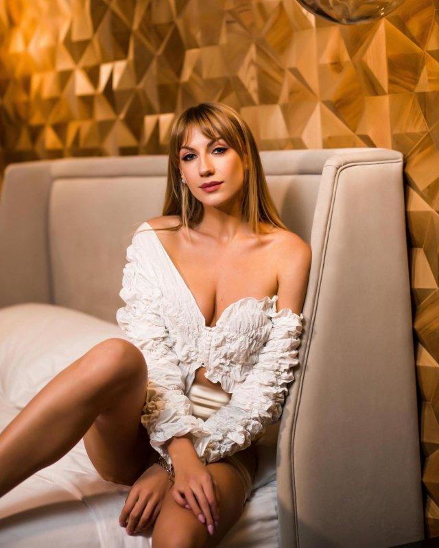 Леся Никитюк в белой кофте сидит на кресле