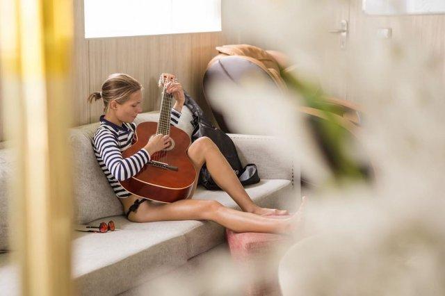 Марина Кацуба в полосатой кофте с гитарой