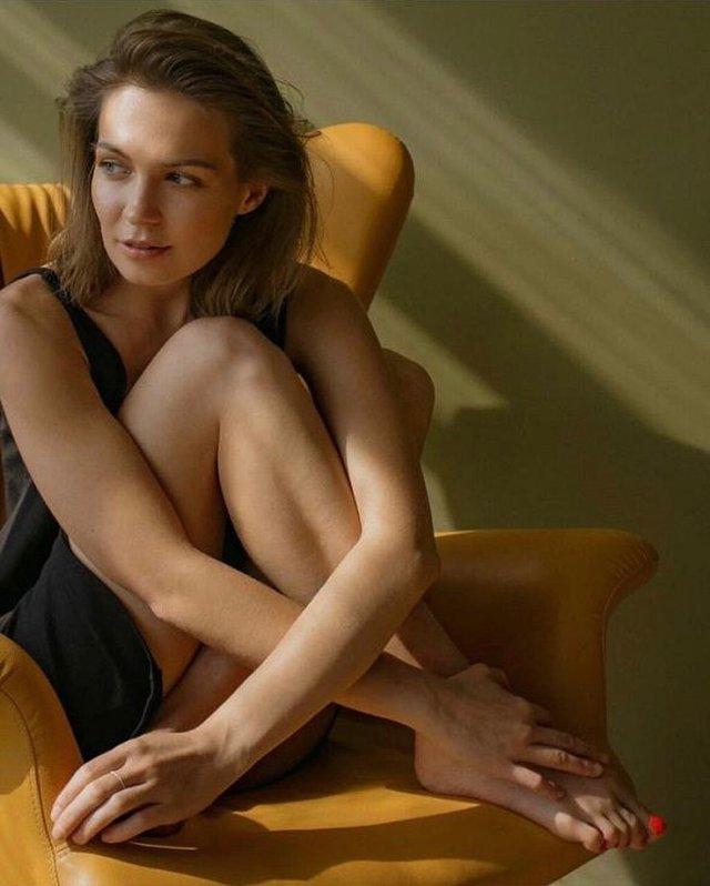 Марина Кацуба в черном платье сидит в кресле
