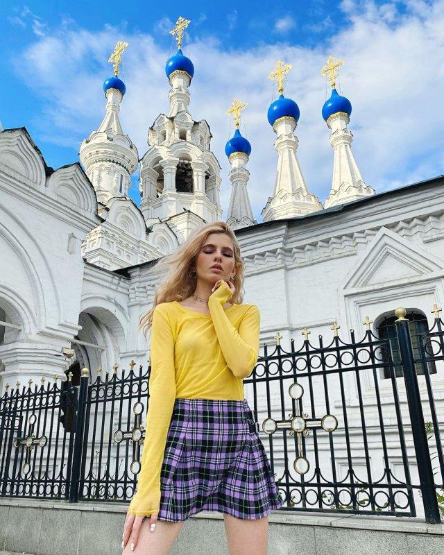 Блогер Алена Ефремова (_cyberbabe_) желтой кофте и клетчатой юбке на фоне церкив