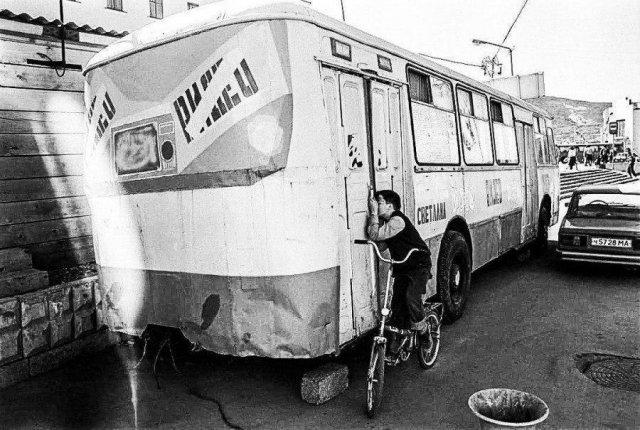 Мальчик подсматривает за показом фильма в видеосалоне, который находится в автобусе. Магадан, 1994 год.