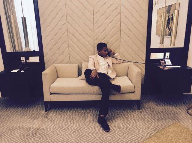 Чоузен Джейкобс в на белом диване разгвоаривает по телефону