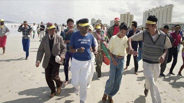 Вопреки законам апартеида, архиепископ Десмонд Туту (в голубом) и его сторонники бегают по белоснежному пляжу в Кейптауне. Южная Африка, 1989 год.