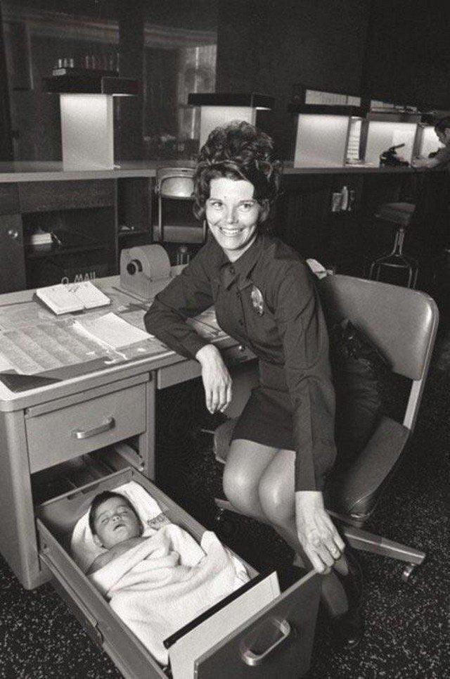 Женщина-полицейский присматривает за брошенным младенцем, бережно уложив его в ящике своего стола. Лос-Анджелес, 1971 г.