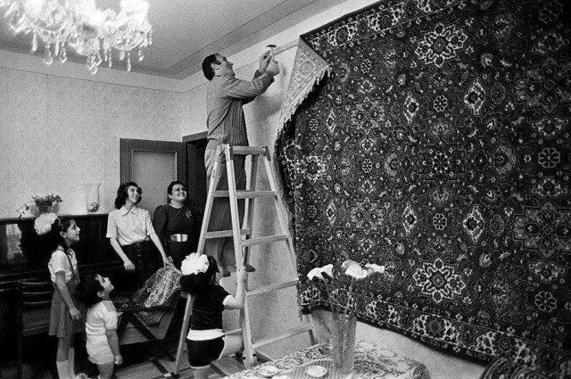 Мужчина прибивает к стене роскошный ковр. СССР. 1970-е