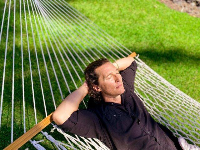 Мэттью МакКонахи в черном рубашке лежит на гамаке