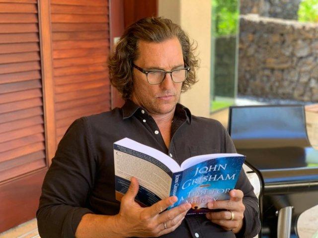 Мэттью МакКонахи в черной кофте читает книгу